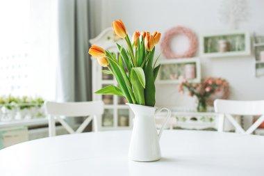 Beautiful orange flowers in vase on rustic kitchen table