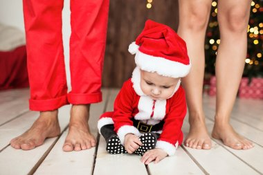 Baby in santa suit with family indoor