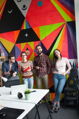 Creative team of four colleagues working in modern office
