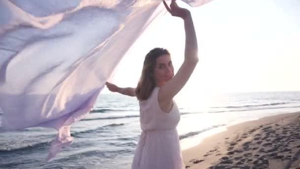 Krásná žena drží Lehká tkanina na pláži a vychutnejte si západ slunce