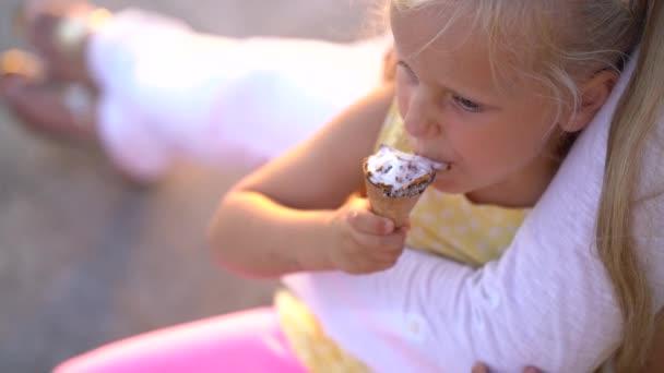 roztomilá holčička jíst zmrzlinu zatímco sedí na promenádě v náručí matky