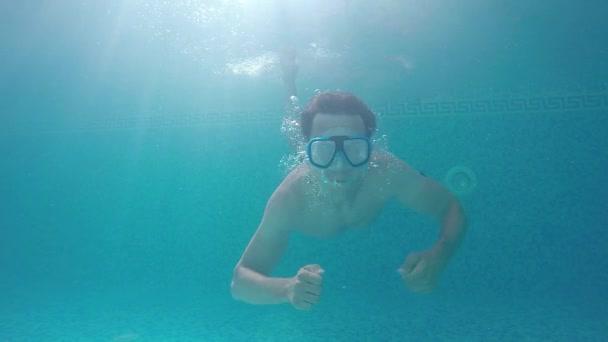 ein junger Mann mit Schwimmmaske unter Wasser hebt den Daumen