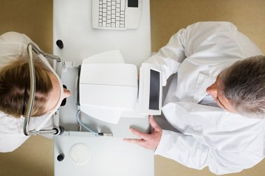 Young woman having her eyes examined by an eye handsome elderly doctor