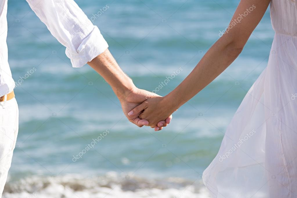happy couple in love walking on the beach