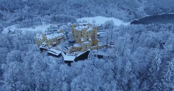 Aerial view of Hohenschwangau Castle at sunrise in winter landscape.