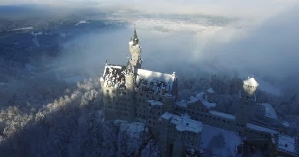 Luftbild von Schloss Neuschwanstein bei Sonnenaufgang in Winterlandschaft