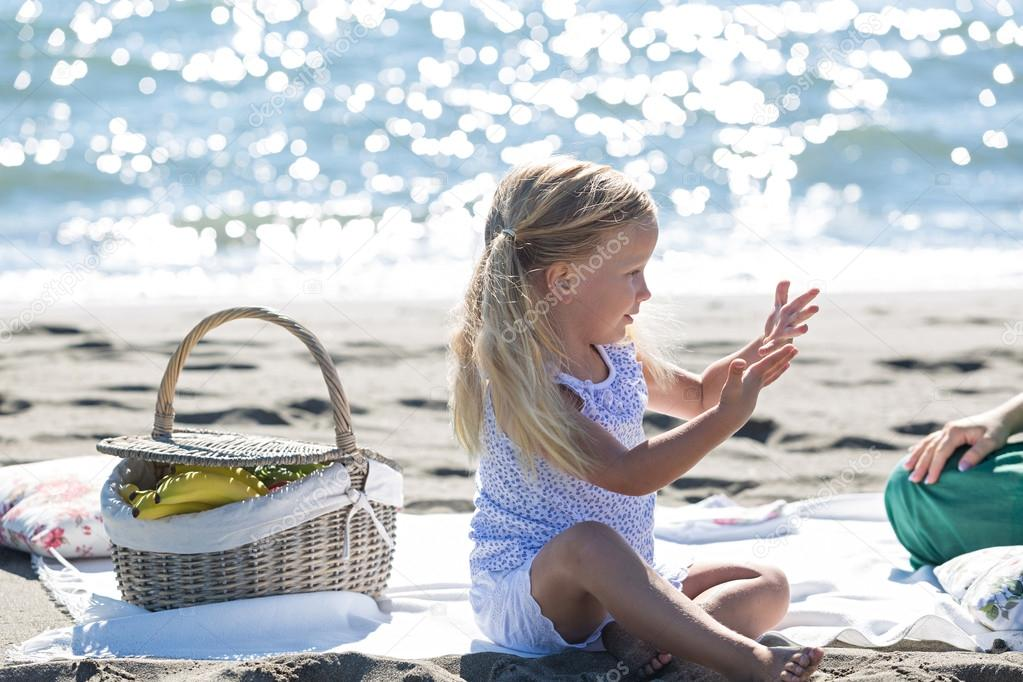 little girl enjoying a picnic on the beach