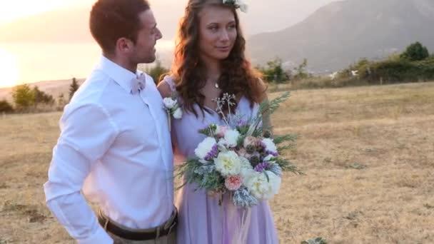 nevěsta a ženich pózuje na západ slunce