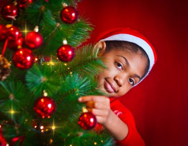 black little girl decorate the Christmas tree