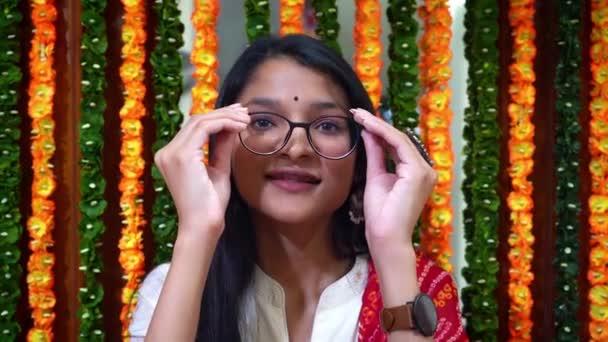 Schöne Inderin, die ihre Brille abnimmt und in die Kamera blickt - Inderin mit bunten Girlanden im Hintergrund In Agra India - mittlere Einstellung
