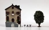 Ein weißer Würfel mit dem Wort STEUER und einem Miniaturhaus. Das Konzept der Erhöhung der Grundsteuern.