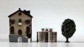 Das Wort STEUER auf weißen Würfeln auf einem Haufen Münzen zwischen Miniaturhäusern und Miniaturbäumen.