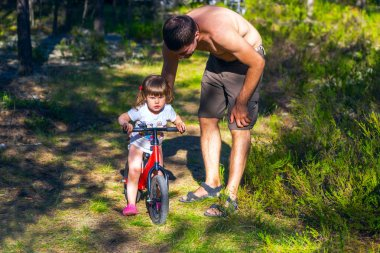 Young father helping daughter to ride  Bicycle.