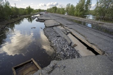 The consequences of the flood washed  road with sagging plates