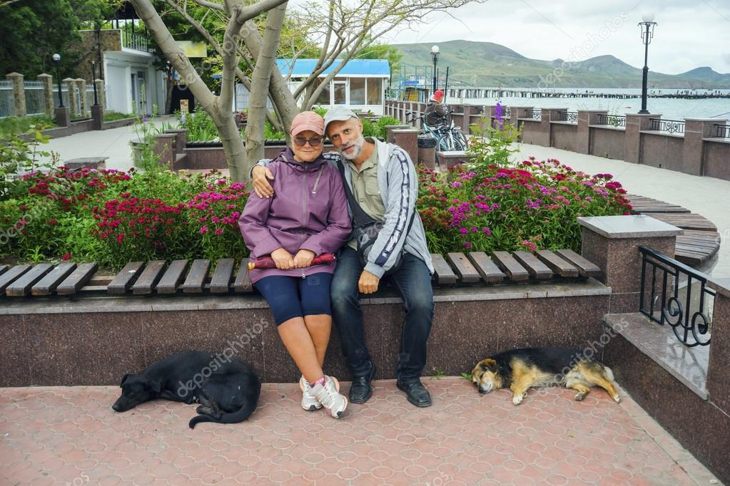 Man and woman embracing sitting on  bench next to lay two dogs .