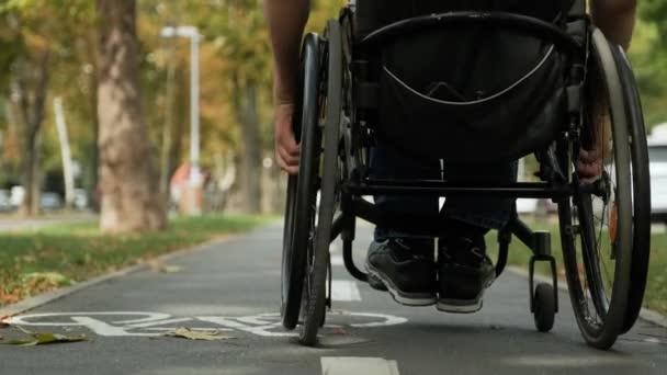 Gehbehinderter Mann im Rollstuhl an der Parkallee