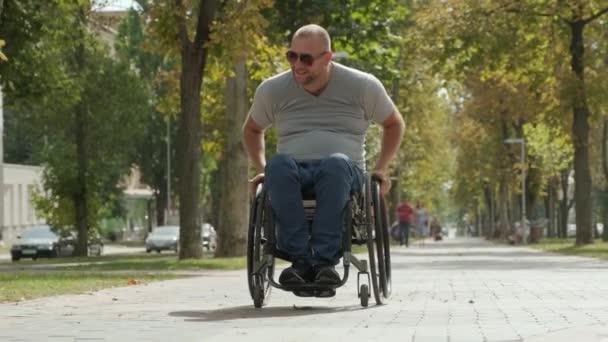 Glücklicher gehbehinderter Mann im Rollstuhl an der Parkallee