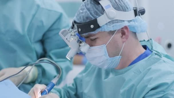 Operation to remove tonsils. In modern clinic under deep anesthesia, using latest devices patient removes glands, cold plasma method, cuts swelling in throat, doctor works with new probe, close-up, new medical technologies
