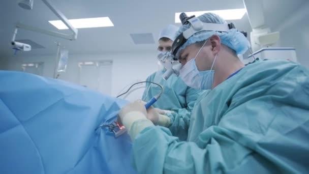 Operation der Mandelentfernung unter Tiefenanästhesie, Chirurg verwendet neueste Geräte, Kaltplasma-Methode, Schnittwunden im Hals, Arzt arbeitet mit neuer Sonde, medizinischer Stirnlampe, Operationslupen