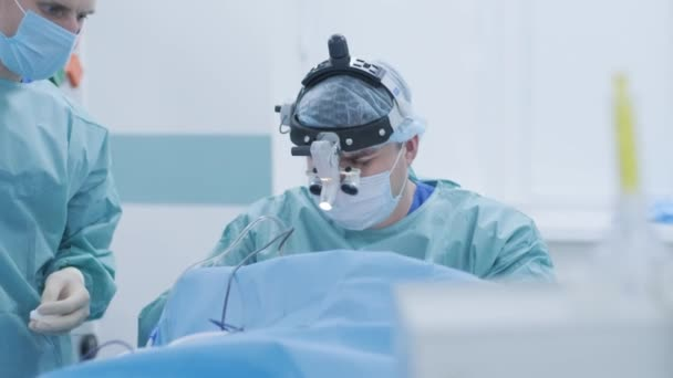 Operation of removing tonsils under deep anesthesia, surgeon uses latest devices, cold plasma method, cuts swelling in throat, doctor works with new probe, medical headlamp, surgical loupes