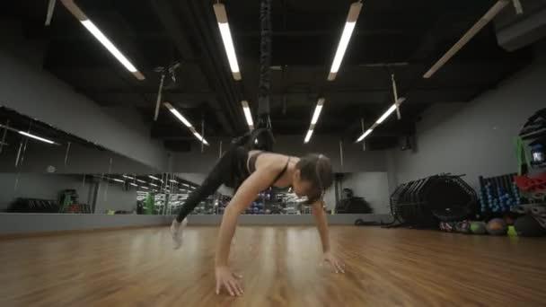 Frauentraining im Fitnessstudio durch Bungee-Training, schwierige Übungen, Bungee-Fitness, moderner aktiver Sport