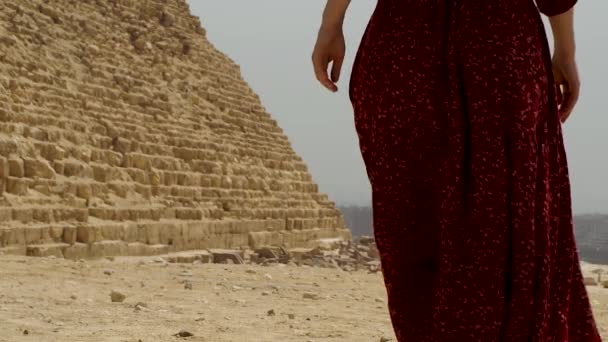 a woman in a long dress passes next to the pyramid of Giza