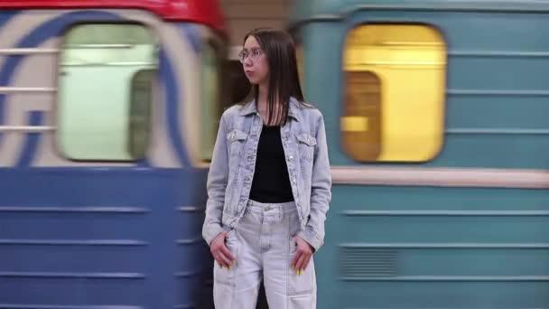 Eine junge Frau steht auf dem Bahnsteig einer U-Bahn-Station und wartet. Menschen mit öffentlichen Verkehrsmitteln pendeln im Stadtgebiet. Eine junge Frau im Hintergrund einer fahrenden U-Bahn
