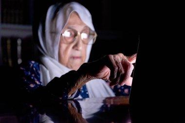 Arap yaşlı Müslüman kadın karanlık odada tabletini kullanıyor.