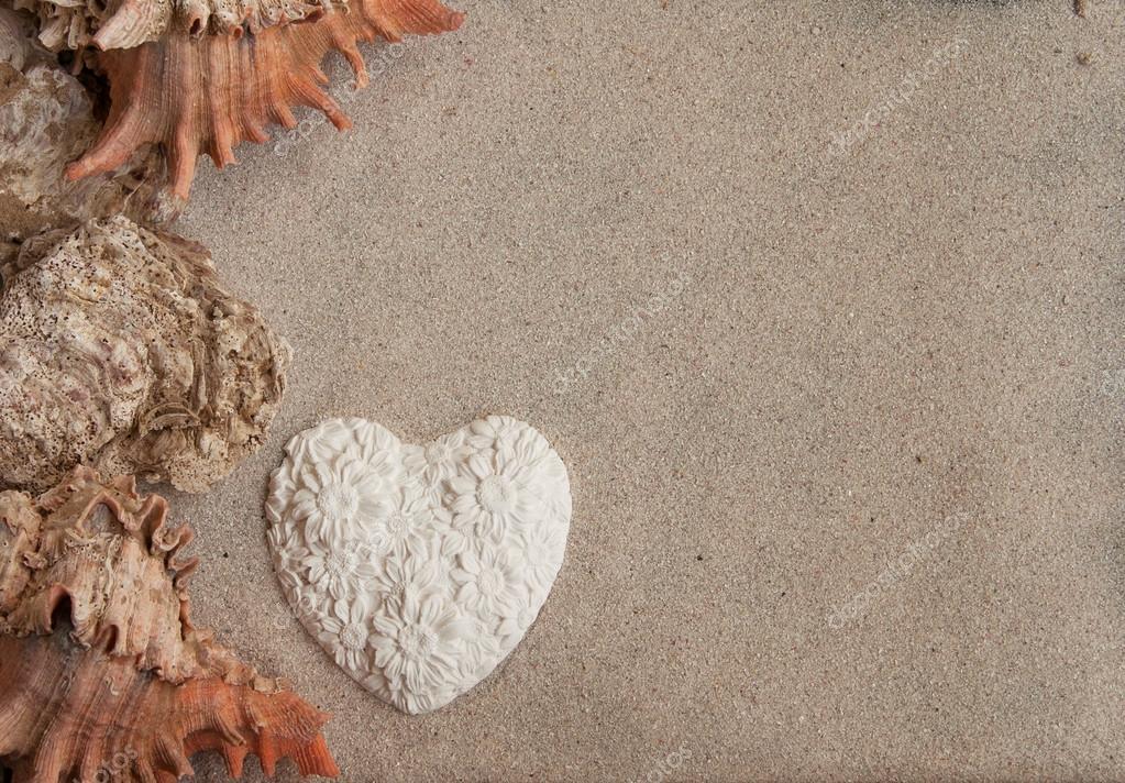 Seashells heart and sand background horizontal