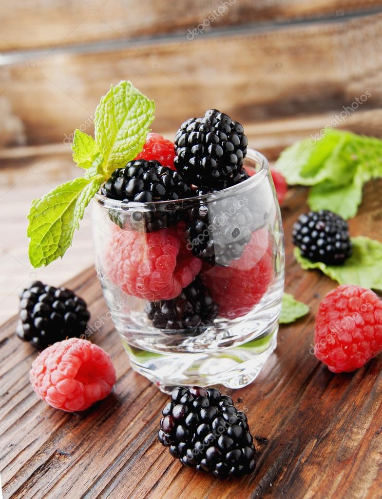 black berries and raspberries in a glass cup