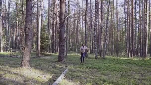 Muž s dlouhými vlasy běží lesem s nožem v ruce.
