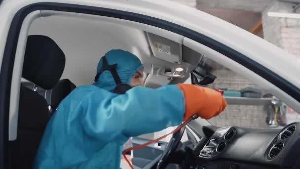 Ein Mann sitzt im Schutzanzug in einem Auto und wäscht das Armaturenbrett. In seinen Händen liegt ein spezielles Werkzeug.