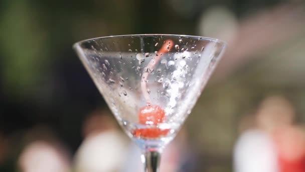 Egy gyönyörű cseresznye fekszik egy pohár borban. Nagyon szép közelkép. Hűvös fény
