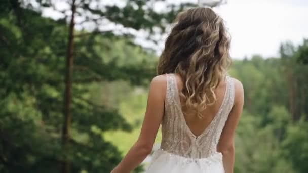 Ein Mädchen im weißen Kleid dreht sich im Wald vor dem Hintergrund der Natur um. Zeitlupenbilder