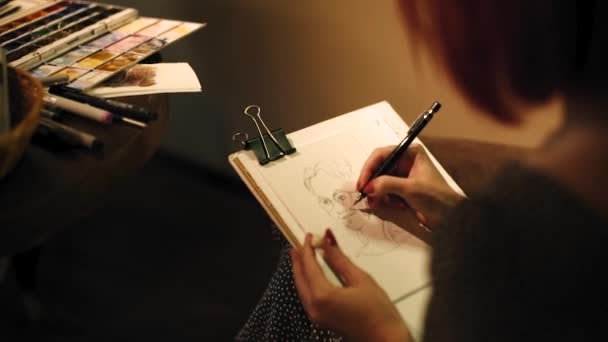 A girl draws cartoons in a paper notebook for guests at the event. Shooting from behind the shoulder