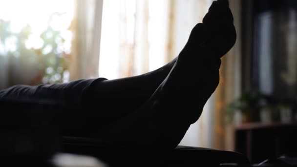 The silhouette of a woman's feet on the background of a light window. The girl is resting lying on the couch. Close-up shooting