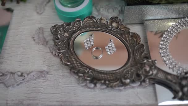 There are jewels on a mirrored tray. Shooting holiday decoration items