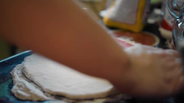 Das Mädchen formt aus dem Teig mit einem Nudelholz einen großen Pfannkuchen. Nahaufnahme des Kochprozesses