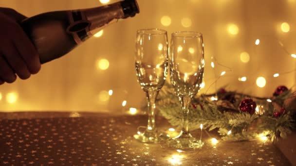 Champagner in zwei Gläser vor dem Hintergrund goldener Lichter gießen