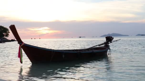 Traditional longtail boat floating on sea water at evening twilight sunset with dramatic orang sky, beautiful relaxing scene of tropical summer sea beach, Koh Lipe island, Thailand.
