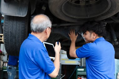 Two mechanic checking wheel at garage, car service technician check and repair customer car at automobile service, senior and young work together at vehicle repair service shop concept