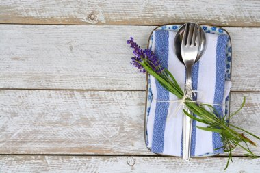 silver cutlery and a blue white napkin kitchen towel with lavender decoration and empty copy space in rustic vintage country style