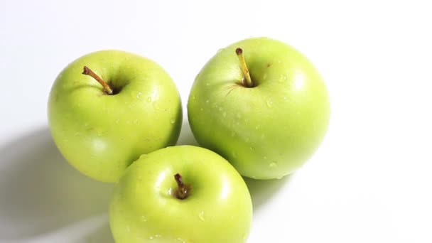 three green sweet apples in drops on a white background. Selective shot.