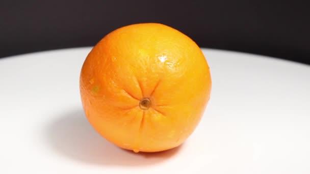 Kerek érett narancs a vízcseppekben közelkép. Szelektív lövés.