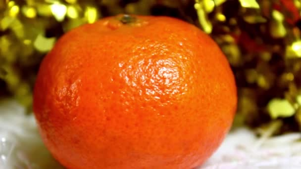 Tangerine on a New Years background with shiny tinsel. Turntable. Close-up.