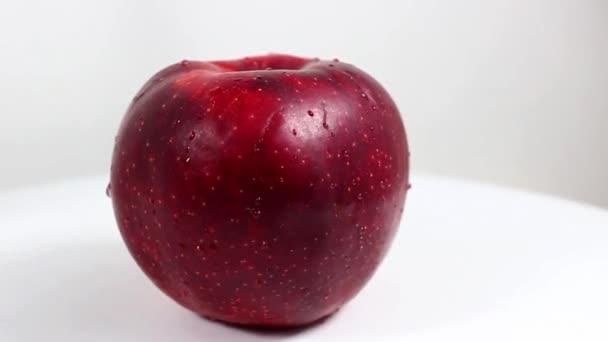 Jedno velké červené jablko zblízka. Otočný stůl. Selektivní snímek.