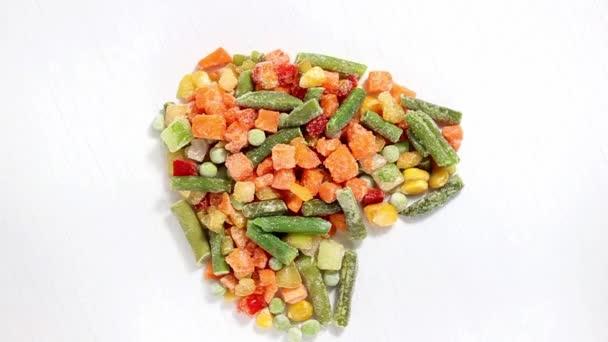 Die gefrorene Gemüsemischung liegt auf einer hellen herzförmigen Oberfläche. Draufsicht, selektiver Fokus.