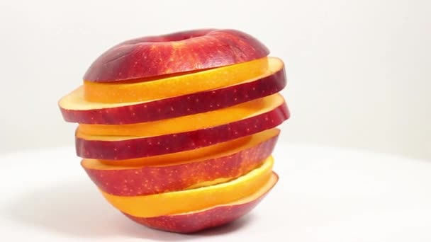 Round slices of red apple and orange are stacked on top of each other in a pyramid on a rotating table. Close-up.