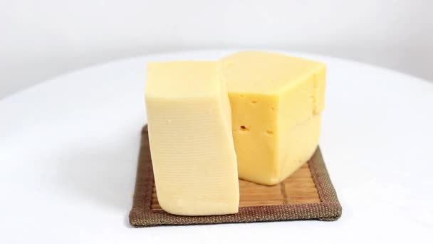 Brikety z krájených kusů tvrdého sýra na otočném povrchu. Detailní záběr, selektivní snímek.