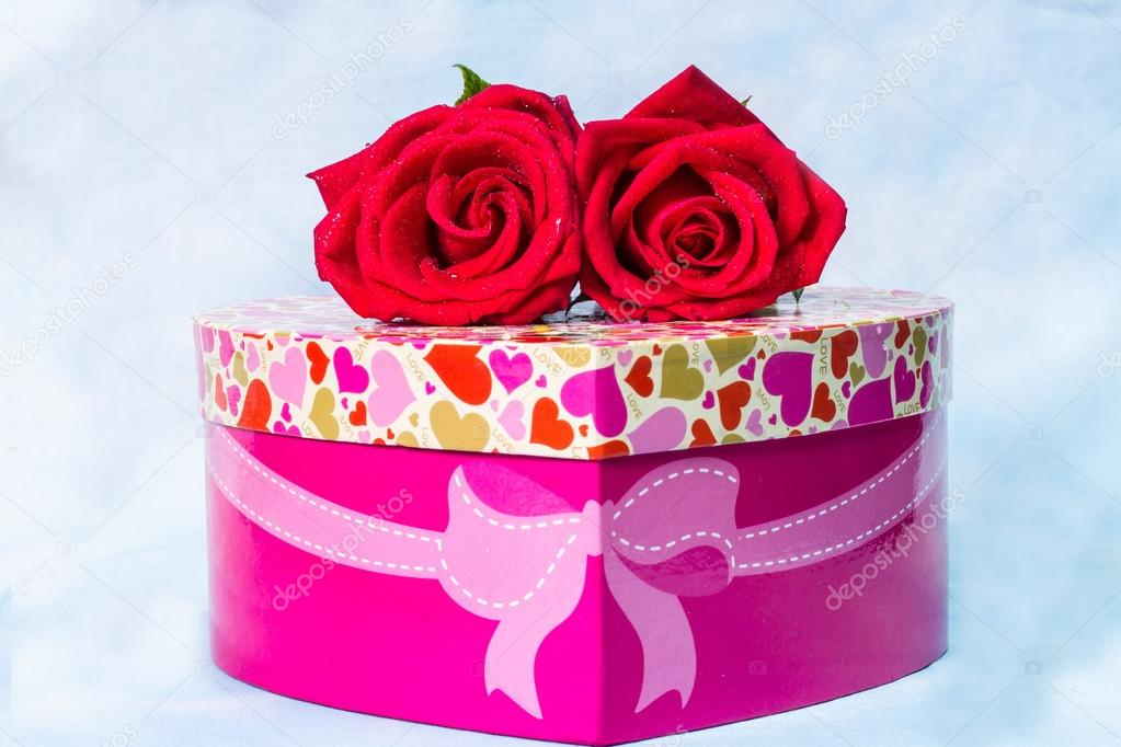 Heart-shaped Valentines Day gift box with red rose over a Backg